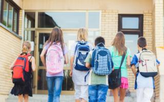 children walking into school with backpacks