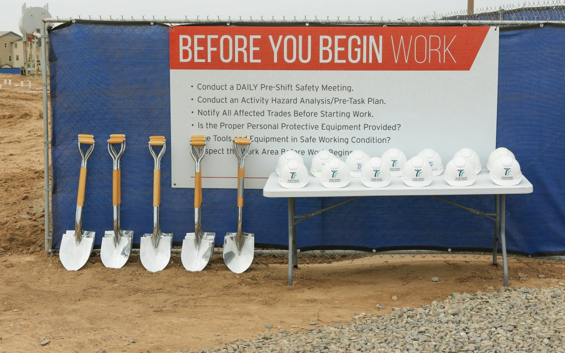 Ceremonial shovels and hard hats lined up
