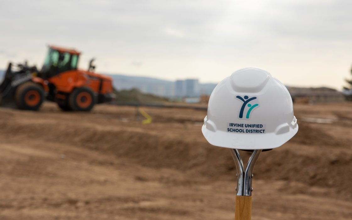 IUSD hard hat in front of construction site