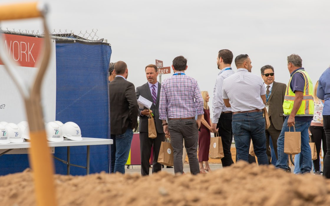 Terry Walker and guests conversing at construction site
