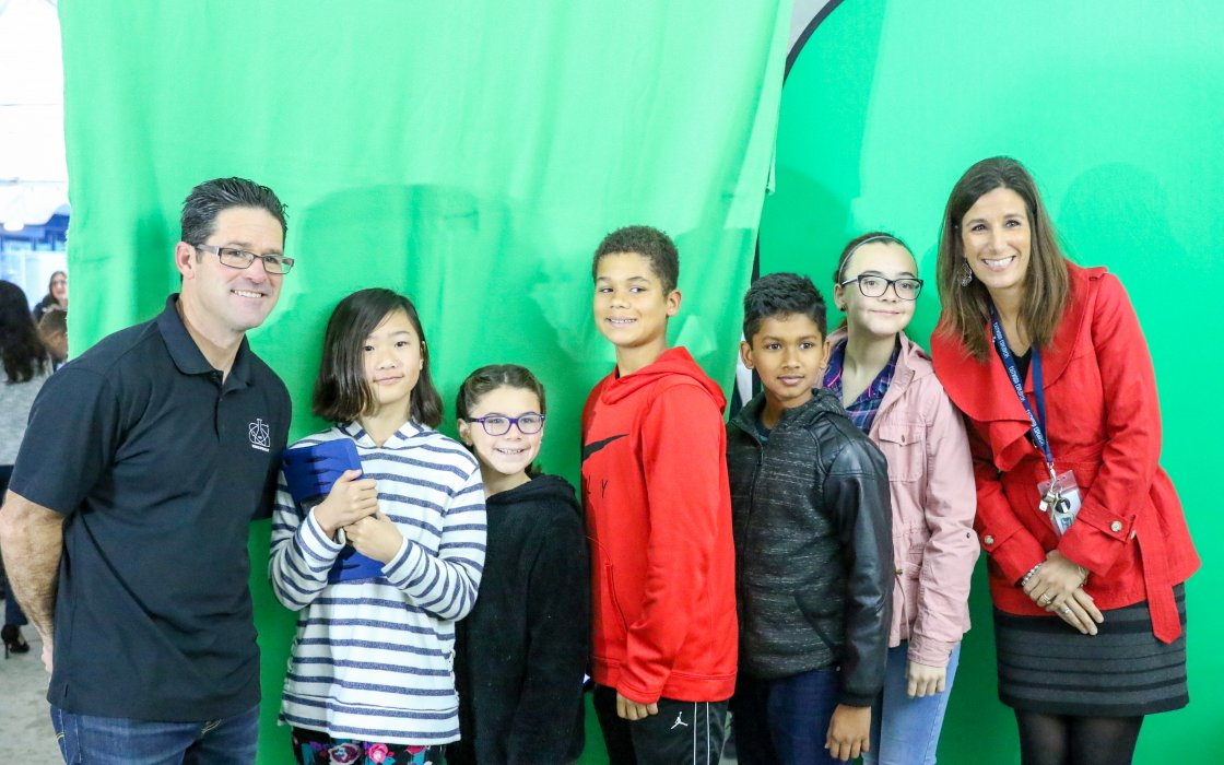 students and teachers with green screen