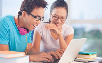 Two students looking at a laptop
