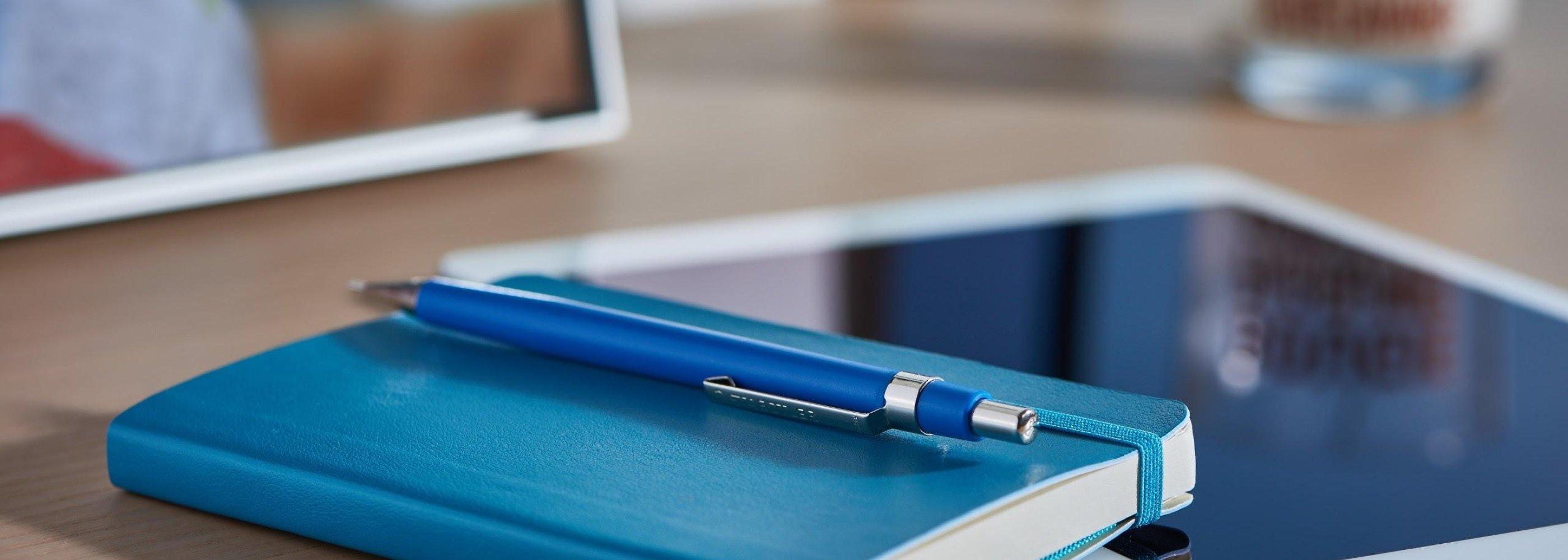 خودکار، کتاب، کامپیوتر روی یک میز