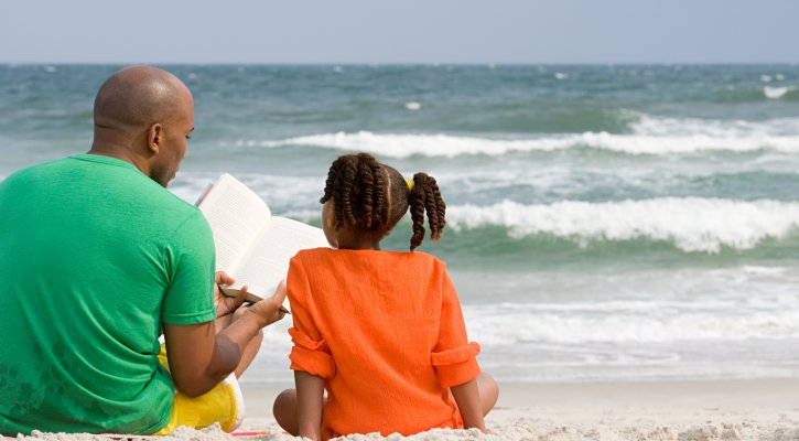 Father and daughter reading on the beach
